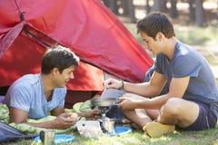 Deux jeunes hommes faisant cuire sur le fourneau de camping en dehors de la tente Image stock