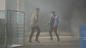 Deux jeunes hommes habiles dansant dans la salle sombre et poussiéreuse du bâtiment abandonné Les types entreprenant des démarche banque de vidéos
