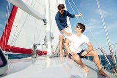 Deux jeunes hommes heureux beaux se tenant sur le yacht Photo stock
