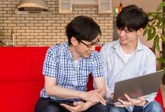 Deux jeunes hommes japonais parlant du contenu sur l'Internet, se reposant sur le sofa à la maison Image libre de droits