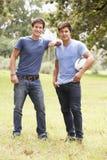 Deux jeunes hommes jouant avec la boule de rugby dans la campagne Images libres de droits
