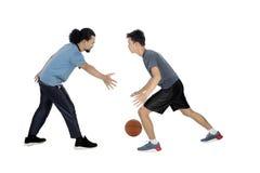 Deux jeunes hommes jouant le basket-ball Photos stock