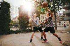 Deux jeunes hommes jouant un jeu de basket-ball Photos stock