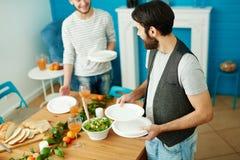 Deux jeunes hommes mettant la table pour la collecte d'amis Images stock