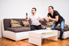 Deux jeunes hommes observant un match de football à la TV L'énergie jeune équipe Images stock