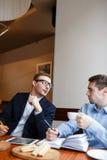 Deux jeunes hommes parlant en café Photographie stock libre de droits