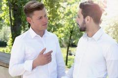 Deux jeunes hommes parlant entre eux en parc Images libres de droits