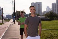 Deux jeunes hommes pulsant par la ville Images libres de droits