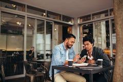 Deux jeunes hommes s'asseyant au café utilisant le téléphone portable Images stock