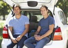 Deux jeunes hommes s'asseyant dans le tronc de la voiture Image stock