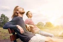 Deux jeunes hommes s'asseyant sur le banc et appréciant le soleil Photo libre de droits