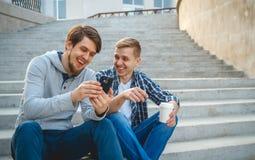 Deux jeunes hommes s'asseyant sur les étapes Image libre de droits