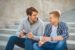 Deux jeunes hommes s'asseyant sur les étapes Photo stock
