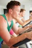 Deux jeunes hommes s'exerçant dans le gymnase sur les machines de recyclage ensemble Images stock