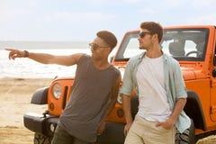 Deux jeunes hommes se tenant ensemble à la plage Photo stock
