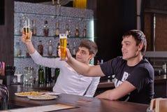 Deux jeunes hommes soulevant leurs bières dans un pain grillé Images stock