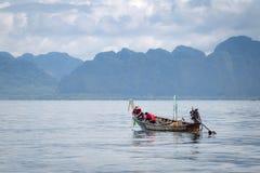 Deux jeunes hommes sur un bateau de pêche dans Krabi, Thaïlande Images stock