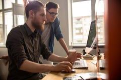 Deux jeunes hommes travaillant avec l'ordinateur Photographie stock libre de droits