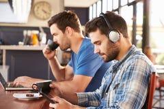 Deux jeunes hommes travaillant sur des ordinateurs à un café photo libre de droits