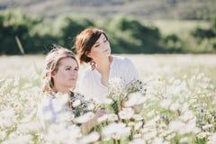 Deux jeunes jolies femmes posant dans une camomille mettent en place Image stock