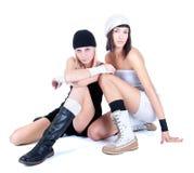 Deux jeunes jolies femmes s'asseyant et posant Photographie stock libre de droits
