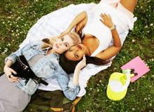 Deux jeunes jolis meilleurs amis de filles d'adolescent s'étendant sur des valeurs maximales de concentration au poste de travail Photo libre de droits