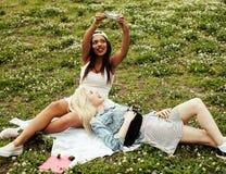 Deux jeunes jolis meilleurs amis de filles d'adolescent s'étendant sur des valeurs maximales de concentration au poste de travail Photos stock