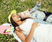 Deux jeunes jolis meilleurs amis de filles d'adolescent s'étendant sur l'herbe faisant la photo de selfie ayant l'amusement, pers Photographie stock