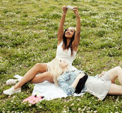 Deux jeunes jolis meilleurs amis de filles d'adolescent s'étendant sur l'herbe faisant la photo de selfie ayant l'amusement, pers Photos libres de droits