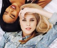 Deux jeunes jolis meilleurs amis de filles d'adolescent s'étendant sur l'herbe faisant la photo de selfie ayant l'amusement, pers Image stock