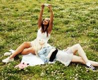 Deux jeunes jolis meilleurs amis de filles d'adolescent s'étendant sur l'herbe faisant la photo de selfie ayant l'amusement, pers Images libres de droits