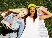 Deux jeunes jolis meilleurs amis de filles d'adolescent s'étendant sur l'herbe faisant la photo de selfie ayant l'amusement, pers Image libre de droits