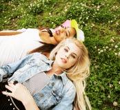 Deux jeunes jolis meilleurs amis de filles d'adolescent s'étendant sur l'herbe faisant la photo de selfie ayant l'amusement, pers Photos stock