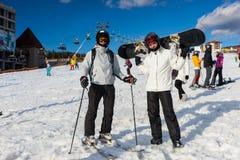 Deux jeunes mâles dans les ski-costumes, les casques et les lunettes de ski tenant W Image stock