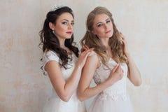 Deux jeunes mariées dans des robes de mariage épousant la brune blonde Image stock