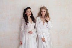 Deux jeunes mariées dans des robes de mariage épousant la brune blonde Photographie stock libre de droits