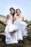 Deux jeunes mariées dans l'hamac contre le ciel bleu avec le fond de forêt Photographie stock