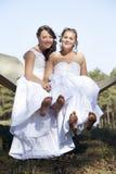 Deux jeunes mariées dans l'hamac contre le ciel bleu avec le fond de forêt Photos stock
