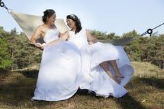 Deux jeunes mariées dans l'hamac contre le ciel bleu avec le fond de forêt Photo libre de droits