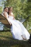 Deux jeunes mariées dans l'hamac contre le ciel bleu avec le fond de forêt Photos libres de droits
