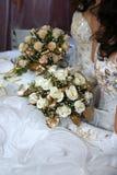 Deux jeunes mariées tenant le bouquet de mariage dans des mains Images stock