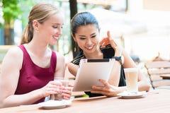 Deux jeunes meilleurs amis féminins à l'aide d'une tablette dehors à un TR Photos stock