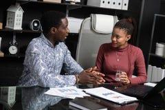Deux jeunes personnes de race noire discuter leurs affaires utilisant des diagrammes se reposant au bureau dans le bureau photos libres de droits