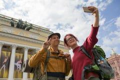 Deux jeunes randonneurs prenant des selfies devant un bâtiment historique Photographie stock