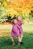 Deux jeunes soeurs caucasiennes frappent une pose en assortissant les robes roses de flanelle image libre de droits