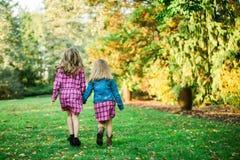 Deux jeunes soeurs caucasiennes marchant loin tenant des mains photographie stock libre de droits