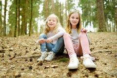 Deux jeunes soeurs mignonnes ayant l'amusement pendant la hausse de forêt la belle journée de printemps tôt Loisirs actifs de fam image libre de droits