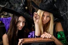 Deux jeunes sorcières devinant sur un tableau noir Images libres de droits