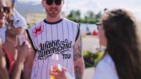 Deux jeunes types attirants parlent à deux filles à une certaine station estivale ensoleillée de plage banque de vidéos