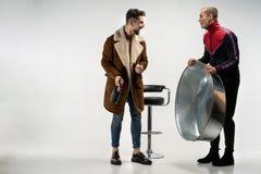 Deux jeunes types beaux dans des vêtements sport se tenant ensemble, tabouret de bar derrière photos libres de droits